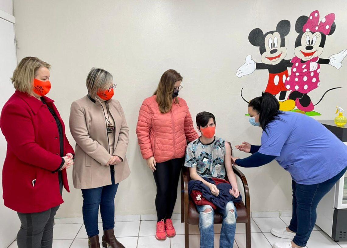 Juan recebeu a primeira dose acompanhado da mãe Juliana, da prefeita Sirlei e da secretária Ana. Foto: Cris Vargas / Prefeitura de Taquara
